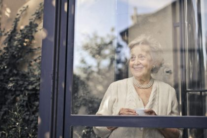 signora anziana dietro una finestra